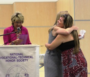 Dental Assisting student Misty Bercume gives her instructor, Kim Bland, a hug as her name is called by career counselor Kathy Matthews at the National Technical Honor Society induction ceremony